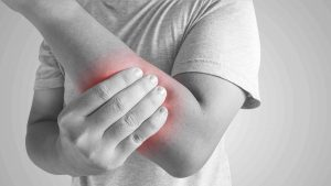 Man grabbing his arm in pain from radial tunnel syndrome